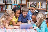 foto of pupils  - Cute pupils looking at tablet in library at the elementary school - JPG