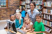 stock photo of pupils  - Cute pupils and teacher looking at computer in library at the elementary school - JPG