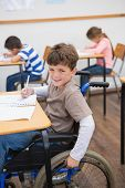picture of disable  - Disabled pupil writing at desk in classroom at the elementary school - JPG