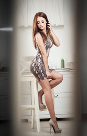 picture of tight dress  - Fashionable attractive young woman in tight short dress sitting on high bar chair - JPG