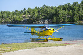 stock photo of float-plane  - Yellow and blue float plane landing on a lake - JPG