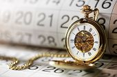 stock photo of time flies  - Pocket watch against a calendar concept for planning or scheduling - JPG