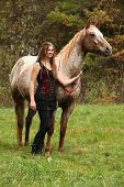 image of appaloosa  - Beautiful girl with nice dress standing next to nice horse in autumn - JPG