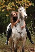foto of appaloosa  - Beautiful girl riding a horse without bridle or saddle in autumn