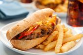 foto of cheesesteak  - cheesesteak sandwich accompanied by fries and an ice cold cola