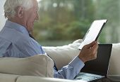 stock photo of retired  - Portrait of retired businessman analyzing business columns - JPG