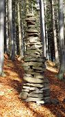 image of troll  - vertical photo of a troll tower made of stones in the wood - JPG