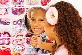 picture of turn-up  - Beautiful small African girl with flower in her hairs reflecting in round mirror while sitting turned back with accessories on background - JPG