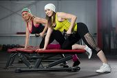 stock photo of workout-girl  - Two smiling sporty pretty girls workout in gym with dumbbells - JPG