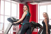 picture of treadmill  - Two sporty girls in sportswear walking on cardio trainer treadmill in gym - JPG