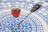 stock photo of blush  - A refreshing glass of blush red wine on a tablecloth with a long shadow from the evening sun - JPG