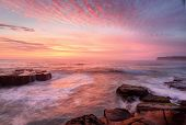 pic of throw up  - Summer sunrise skies light up with colour throwing warmth across the landscape and whitewater seas wash around the rocks at North Avoca Central Coast NSW Australia - JPG