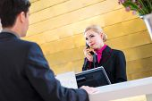 pic of receptionist  - Hotel receptionist telephoning with guest for reservation or information  - JPG
