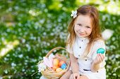 picture of bunny ears  - Above view of adorable little girl wearing bunny ears playing with Easter eggs on a grass covered with white flower petals on spring day - JPG