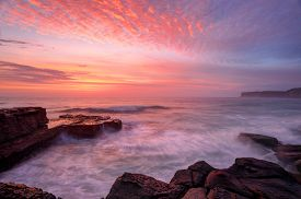 foto of glorious  - Glorious summer sunrise skies over North Avoca rockshelf and a soft sea spray mist and motion in the waves - JPG