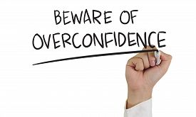 foto of megalomania  - Business concept image of a hand holding marker and write Beware of Overconfidence isolated on white - JPG