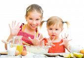 stock photo of little sister  - cute little sisters baking on kitchen and shows hands  on a white background - JPG