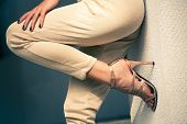 picture of close-up shot  - woman legs in high heel golden sandals and pants lean on wall - JPG