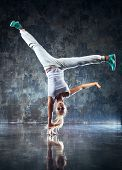 stock photo of wall-stone  - Young woman modern dancer standing on one hand - JPG