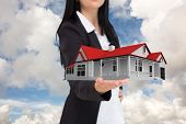 stock photo of presenting  - Pretty businesswoman presenting with hand against blue sky with white clouds - JPG