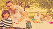 foto of extend  - Father and son at barbecue grill with extended family having lunch in the park - JPG