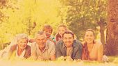 stock photo of extended family  - Portrait of an extended family lying on grass in the park - JPG