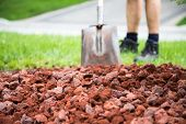 stock photo of shovel  - Man with shovel soft in behind fresh new lava stone in the garden - JPG