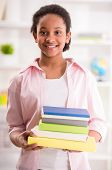 picture of mulatto  - Young smiling mulatto schoolgirl holding stack of books in hands on colorful background - JPG