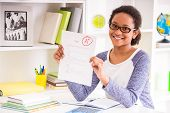 stock photo of mulatto  - Young mulatto schoolgirl in glasses sitting at the table and showing perfect test results on colorful background - JPG