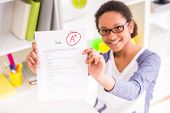 foto of mulatto  - Young mulatto schoolgirl in glasses sitting at the table and showing perfect test results on colorful background - JPG