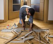 image of leak  - Manual worker disassembling wooden floor ruined from moisture and water leak - JPG