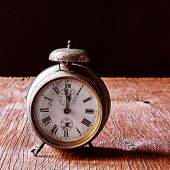 stock photo of wind up clock  - a rusty old alarm clock on a rustic wooden table - JPG
