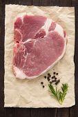stock photo of pork chop  - Raw pork chop steak on wooden background - JPG