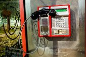 foto of dial pad  - Red public telephone is attached on metallic background phone and headset - JPG