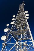 stock photo of antenna  - Communication antenna tower with different antennas on blue sky