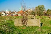 stock photo of suburban city  - Concrete pipes scattered on green meadow with city nearby - JPG
