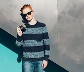 stock photo of redhead  - Young redhead man in a sweater and jeans standing next to green grea wall and taking photos vintage camera - JPG