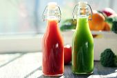 foto of crate  - Bottles of juice with fruits and vegetables  in crate on windowsill - JPG