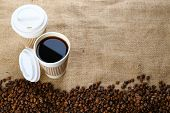 image of sackcloth  - Paper cup of coffee with beans on sackcloth close up - JPG