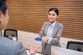 picture of receptionist  - Smiling receptionist giving electronic keys to the guest - JPG