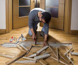 pic of leak  - Manual worker disassembling wooden floor ruined from moisture and water leak - JPG