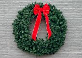 foto of christmas wreath  - a christmas wreath with red bow on gray brick - JPG