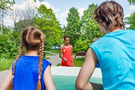 foto of ping pong  - Four teenage friends playing ping pong outside during summer sunny day - JPG