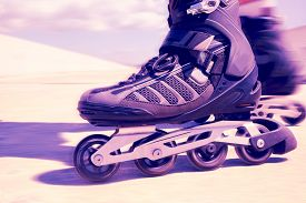 foto of inline skating  - closeup of the feet of a young man roller skating with inline skates - JPG
