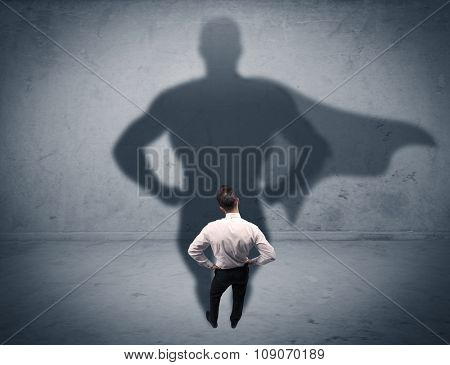 A confident young elegant salesman with briefcase facing a wall, looking at his superman shadow conc