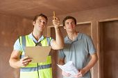 Builder And Inspector Looking At New Property poster