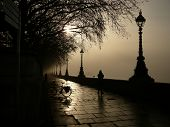 stock photo of lamp post  - Walkway next to the River Thames in London is Silhouetted in the half - JPG