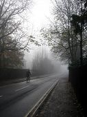 Lonely Cyclist On A Misty Road