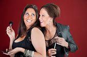 foto of friendship belt  - Two giggling cougers dressed in black prepare their makeup - JPG