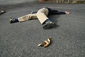 image of prone  - a man who had an accident when he slipped on a banana peel lies on the ground - JPG